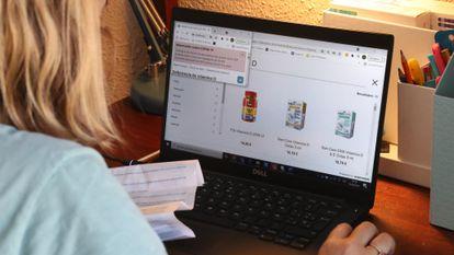 Una jovne compra vitamina D en una farmacia online desde su casa.