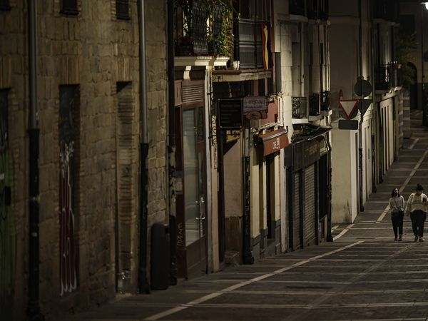 Residents wearing face mask protection as they walk along an empty Javier street, in Pamplona, northern Spain, Saturday, Oct. 24, 2020, as new measures against the coronavirus began in the Navarra province where all bar and restaurants are closed for 15 days from Wednesday midnight. (AP Photo/Alvaro Barrientos)