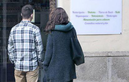 Una pareja, frente a un centro de terapias alternativas en Valencia.