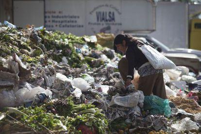 Una mujer busca comida entre los restos en la Central de Abastos de la capital de México.