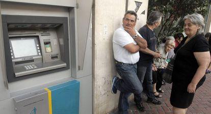 Ciudadanos hacen cola ante una sucursal del Banco Nacional de Grecia