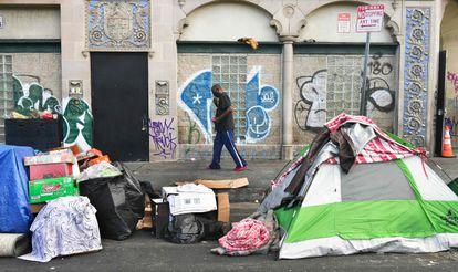 Un hombre pasa frente a tiendas de campaña de personas sin techo en una calle de Los Ángeles en abril de este año.