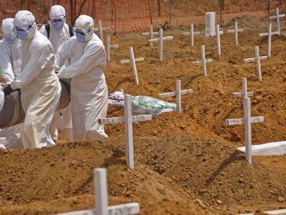 Trabajadores sanitarios llevan el cadáver de una víctima de ébola en un nuevo cementerio en las afueras de Monrovia, Liberia.