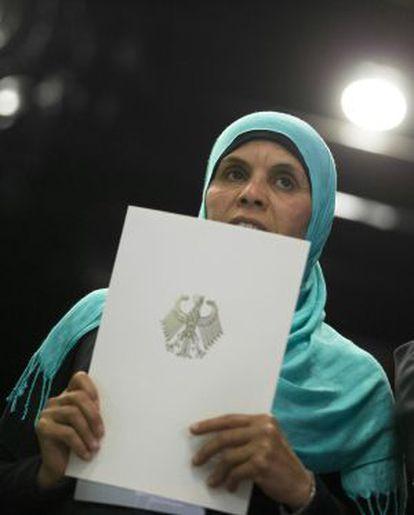 Una mujer nacionalizada sostiene los documentos de su ciudadanía alemana.