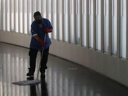 Un trabajador contratado bajo el esquema 'oursourcing' limpia en el Senado de la República.