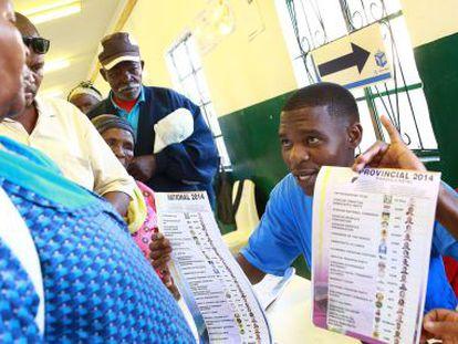 Un miembro de la Comisión Electoral Independiente explica cómo se vota, este miércoles en un colegio electoral de Nkandla (Sudáfrica)