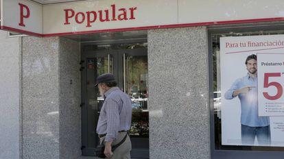 Un hombre pasa ante una oficina del Popular.