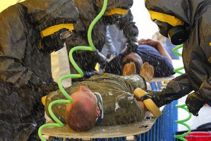 Miembros de un equipo de emergencia realizan un ejercicio de descontaminación en la base aérea de Yokota, en Tokio.