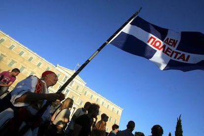 """Manifestantes ondean una bandera griega que dice: """"No en venta"""", en una protesta ayer contras las medidas de austeridad ante el Parlamento."""