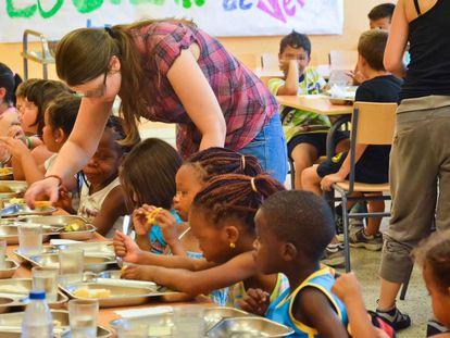 Un grupo de menores almuerza en el comedor escolar de verano.
