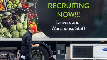 Un trabajador pasa por delante de un camión con un anuncio de contratación, el pasado miércoles en Londres.