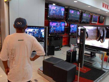 Un hombre mirando pantallas de televisión en Brasil.