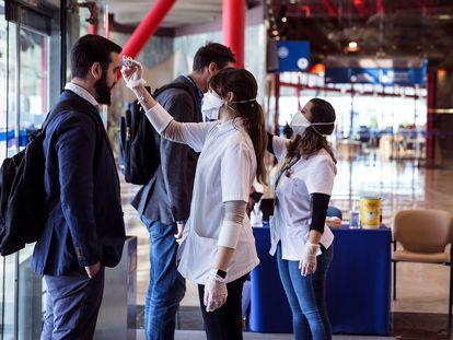 Personal sanitario toma la temperatura corporal a la entrada del Palacio de Ferias y de Congreso de Málaga.