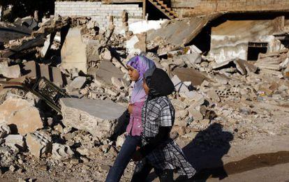 Dos niñas sirias caminan junto a los escombros de una casa derribada durante un bombardeo de las fuerzas pro-régimen.