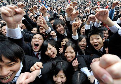 Los estudiantes universitarios japoneses elevan sus puños y gritan durante la ceremonia anual de la búsqueda de empleo en Tokio.
