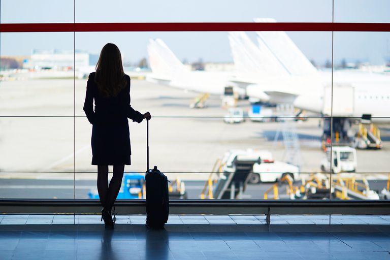 Viajera de negocios frente a una ventana en un aeropuerto.