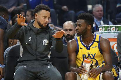Andrew Wiggins, a la derecha, habla con Stephen Curry durante un partido entre Golden State y Nueva Orelans en febrero de 2020.