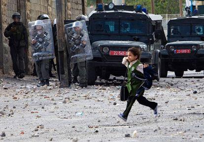 Una escolar palestina pasa delante de efectivos israelíes, en medio de los distubios, en Cisjordania.