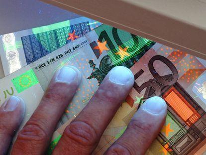 Comprobación de la autencidad de unos billetes mediante luz ultravioleta.
