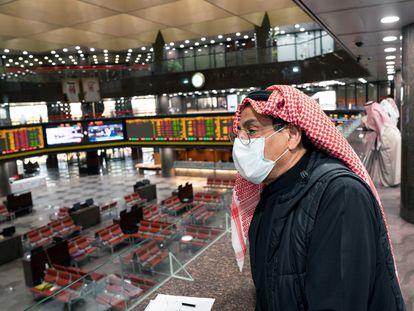 Trabajador con mascarilla en la bolsa de Kuwait.