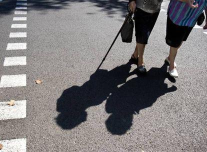 Una pareja de ancianas pasea por una calle de Barcelona en un día de verano.