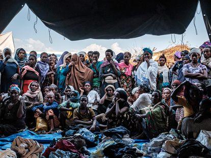 Un grupo de personas desplazadas que huyen de la violencia en la zona de Metekel, al oeste de Etiopía, se reúnen fuera de una carpa donde se distribuye ropa en un campamento en Chagni, Etiopía el pasado 26 de enero de 2021.