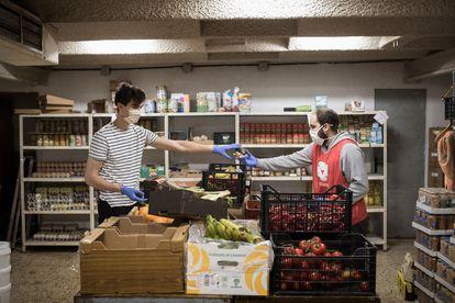 Dos voluntarios de la ONG De Veí a veí cargando cajas de alimentos para usuarios de la entidad.