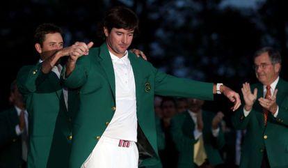 Watson recibe la chaqueta verde de manos de Schwartzel.