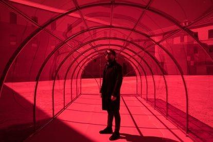 El artista Patrick Hamilton posa con su obra 'El invernadero rojo', en el patio del Centro Condeduque, para MadBlue 2021.