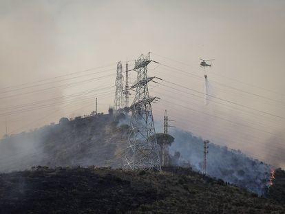 Dotaciones aéreas de los bomberos trabajan en la extinción del incendio en Collserola.