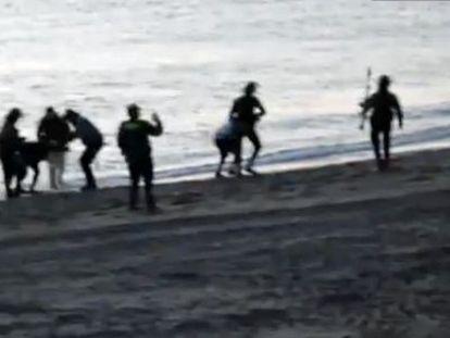 Los guardias civiles devuelven a inmigrantes a Marruecos en la playa deTarajal.