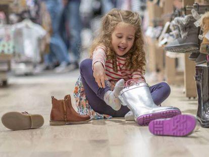 Una niña se prueba zapatos en una tienda.