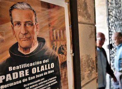 Dos hombres pasan el jueves junto a un cartel que anuncia la beatificación del padre José Olallo.