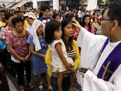 Católicos romanos esperan para que les marquen de ceniza su frente.