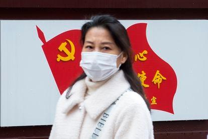 Una mujer pasa delante de una bandera del Partido Comunista