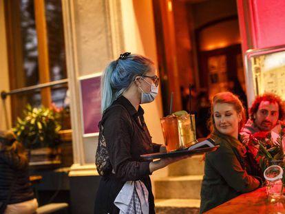 Stephanie Llynch sirve un cocktail a unos clientes cuando los bares de Berlín acaban de abrir de nuevo al público tras la crisis de Coronavirus.