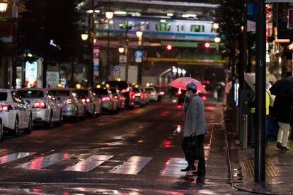 Un hombre camina por una intersección hacia una estación de tren en Tokio el pasado marzo.