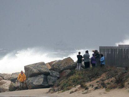 Varias personas observan las olas, en la playa de La Pineda, en Vilaseca (Tarragona), este martes. / En vídeo, el paso de la DANA por la Península, este lunes.