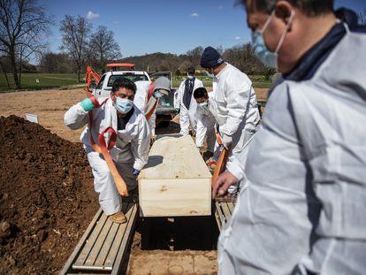 Trabajadores funerarios llevan un cuerpo de una víctima por covid en Staten Island, Nueva York, en una imagen del 6 de abril.