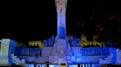 El monumento a las Cortes de 1812, en Cádiz, iluminado con luces azules.