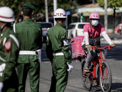 Un repartidor pasa junto a varios militares, este martes en Rangún (Myanmar).