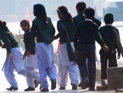 Un grupo de escolares de la escuela atacada en Peshawar (Pakistán) se aleja del lugar del atentado.