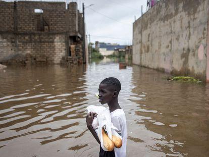 Un niño con dos barras de pan en una calle completamente inundada del barrio de Keur Massar, a las afueras de Dakar, este viernes 20 de agosto.