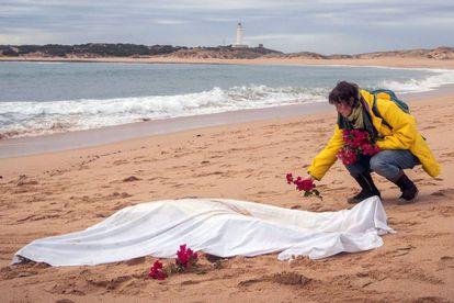 Una mujer coloca flores junto al cadáver de un inmigrante que murió en un naufragio cerca de la costa de Cádiz.
