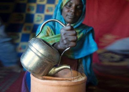 Una refugiada saharaui utiliza un zeer, un refrigerador casero hecho con arena, en Argelia.