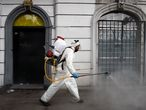 A cleaning worker wearing personal protective equipment (PPE) disinfects a street in Mexico City, on May 7, 2020, amid the new coronavirus pandemic. (Photo by ALFREDO ESTRELLA / AFP)