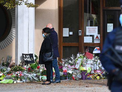 Dos personas pasean junto a la alfombra floral en homenaje al profesor asesinado en Francia