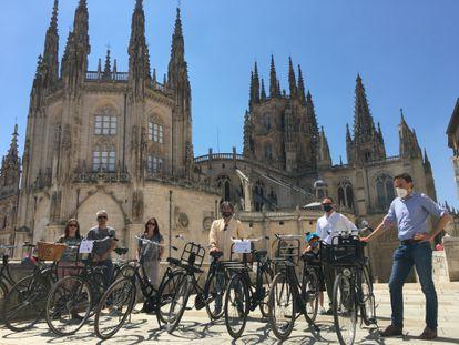 Varias personas posan con sus bicicletas holandesas junto a la catedral de Burgos.