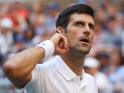 Novak Djokovic se lleva la mano a la oreja durante el partido contra Nishikori en la tercera ronda.