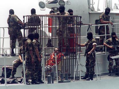 Abimael Guzmán rodeado de policías  el 3 de abril de 1993, mientras es trasladado en barco desde la cárcel de la isla a una prisión en tierra firme.
